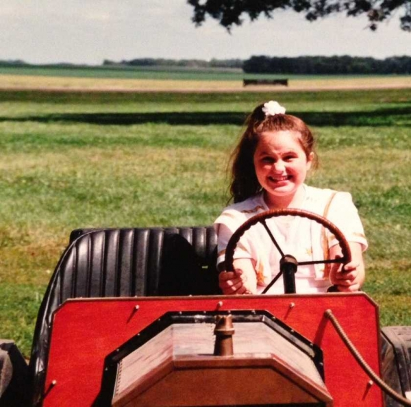 Childhood photo of Gillian Hammond, sitting in a bright red toy truck.