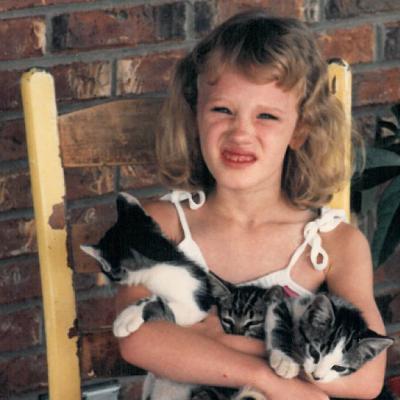 Childhood photo of BrandFuel employee Allison McLain holding a cat.