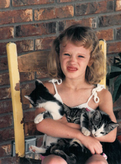 Childhood photo of BrandFuel employee Allison McLain holding a cat.