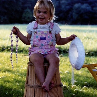 Childhood photo of BrandFuel employee Bridget Ray holding a hat and necklace.