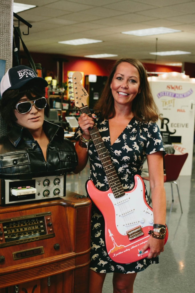 Brooks smiling and holding an electric guitar next to an Elvis diplsay.