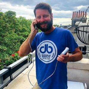 Photo of BrandFuel employee Alex Stowe talking on his smart phone.