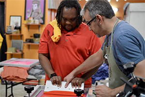 """Two men working on a shirt during the """"Make and Bake"""" event."""