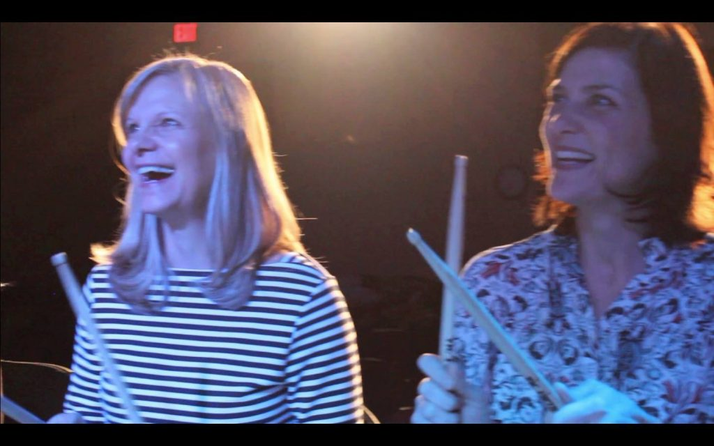 Two ladies enjoying the show and holding drum sticks.