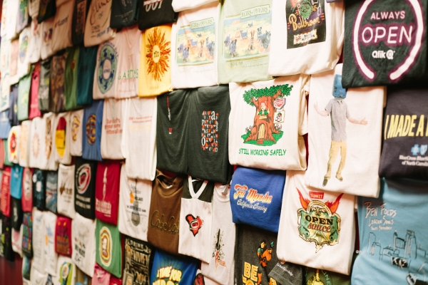 Wall of t-shirts with different designs and colors