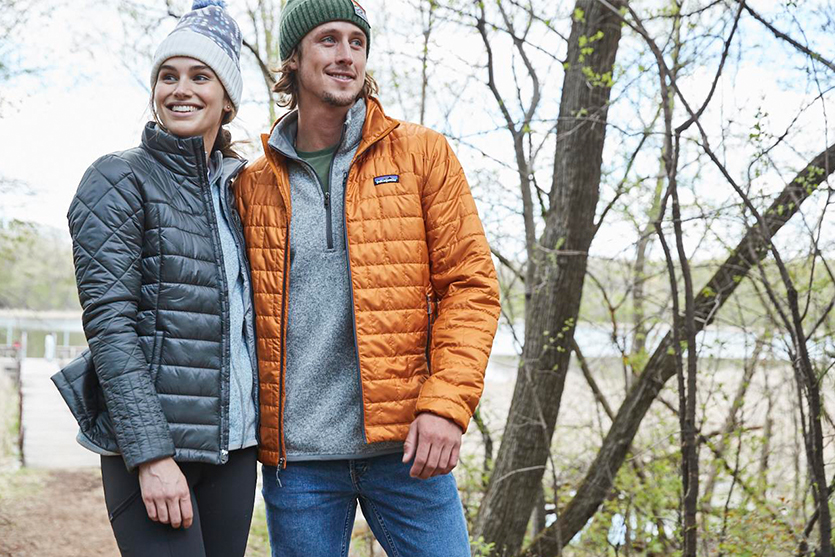 A woman and man wearing Patagonia jackets while hiking.