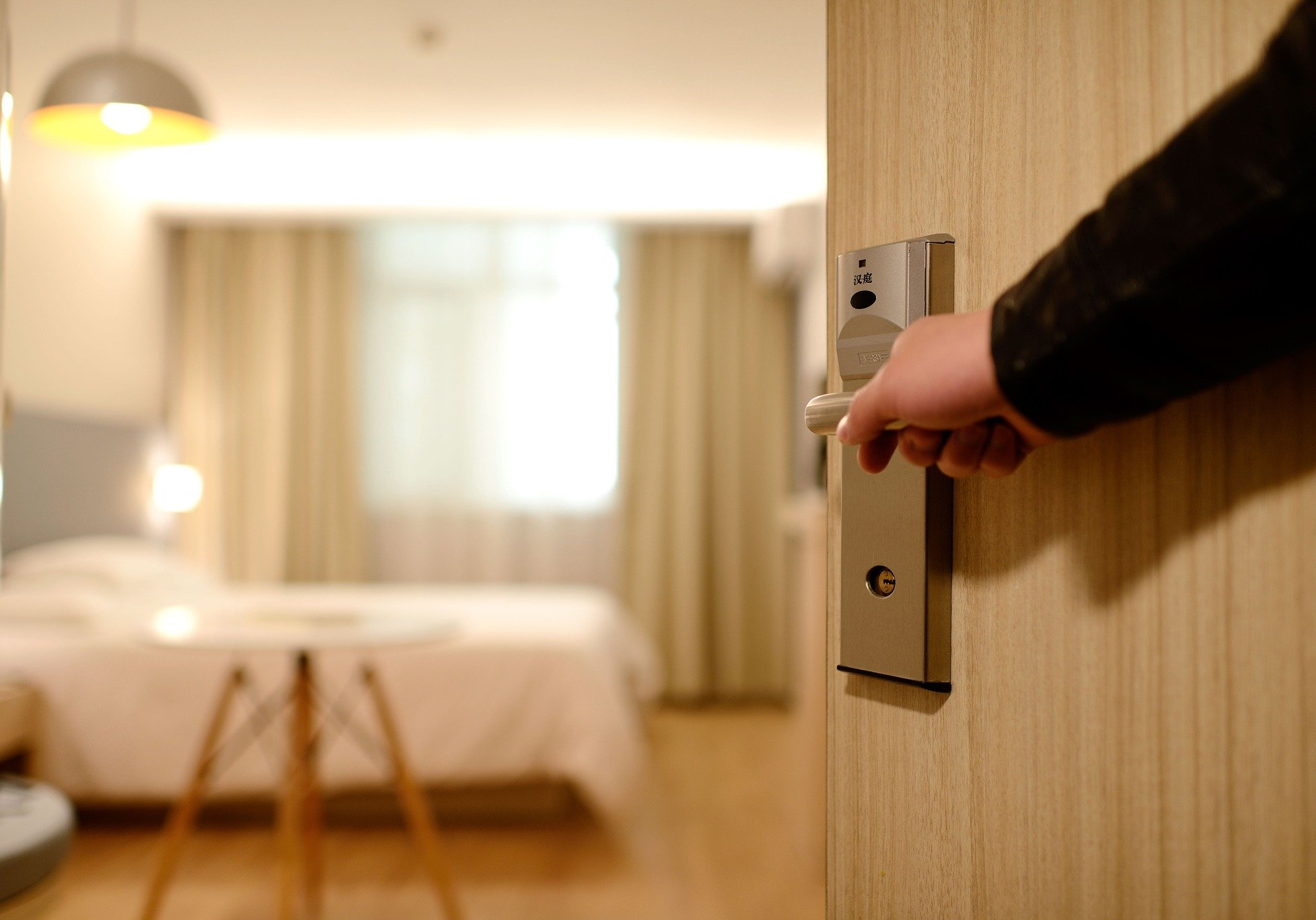 A person opening a hotel door and looking into the room.