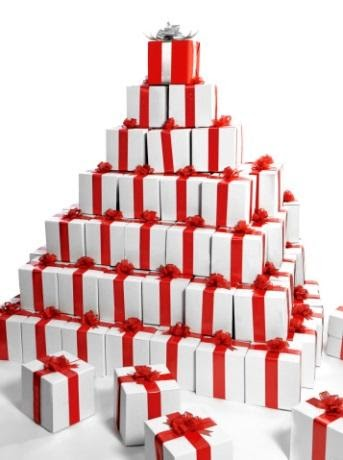 A pyramid of gifts with red bows on them. The top gift is a red box with a white bow.