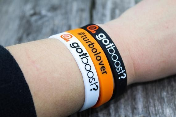 """A white, orange, and black wrist band saying """"got boost?"""" and """"turbo lover."""""""