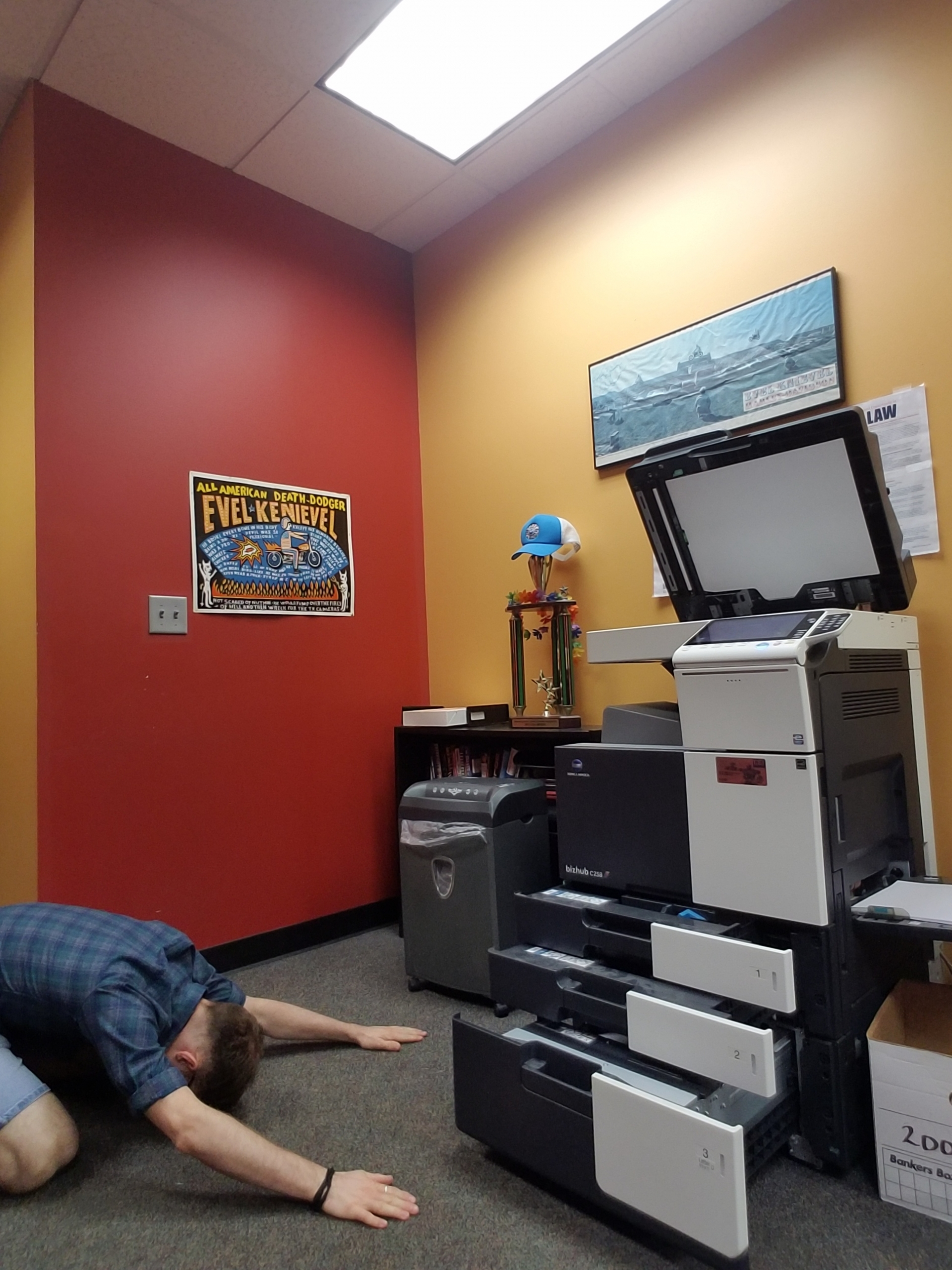 BrandFuel employee Blake Waller bowing down to a copy machine