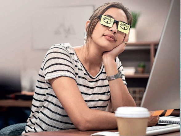 A woman sleeping during work with eyes drawn on to Post It notes and stuck to her glasses.